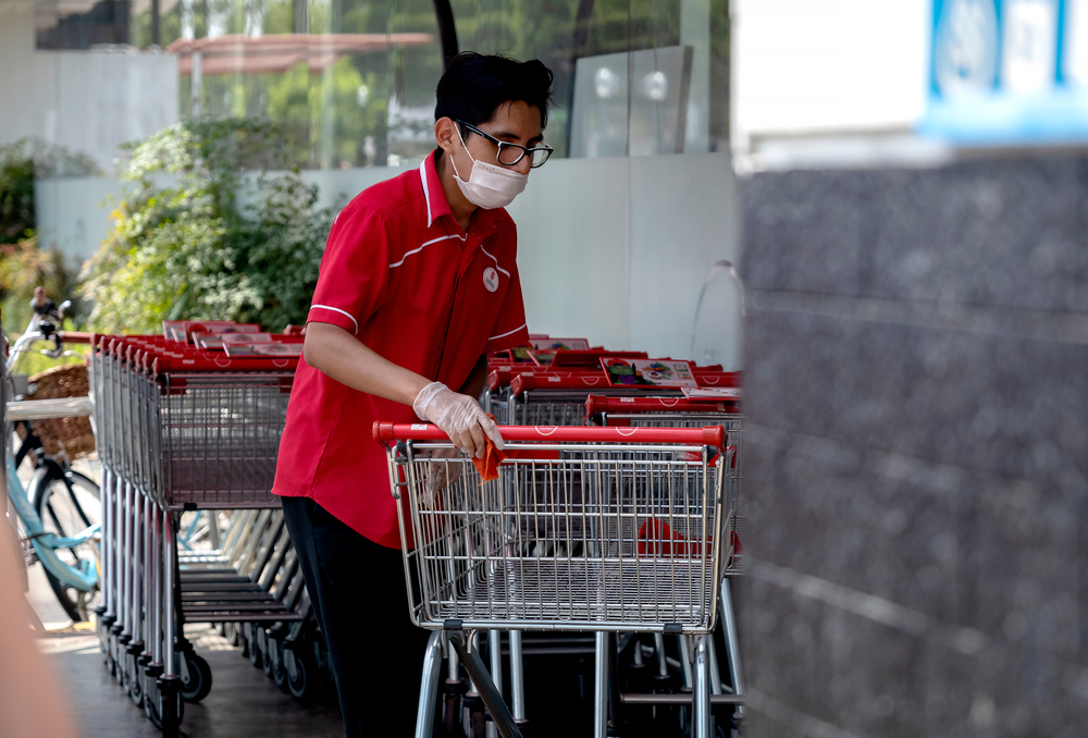 Supermarket worker disinfecting shopping carts and wearing a mask amid coronavirus outbreak in South America. Cleaning shopping carts outside a Wong store in COVID-19 times.